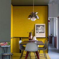 Стол для приема пищи возле желтой стены