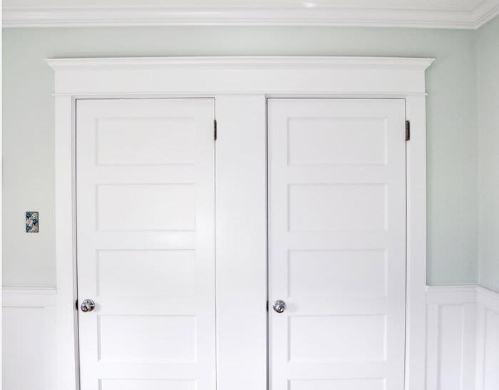 Отделка дверного проема белыми молдингами