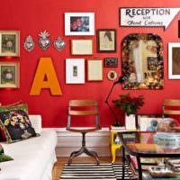 Буква и картины на красной стене гостиного помещения