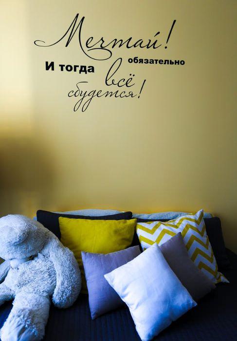 Надпись над диваном в интерьере жилого дома