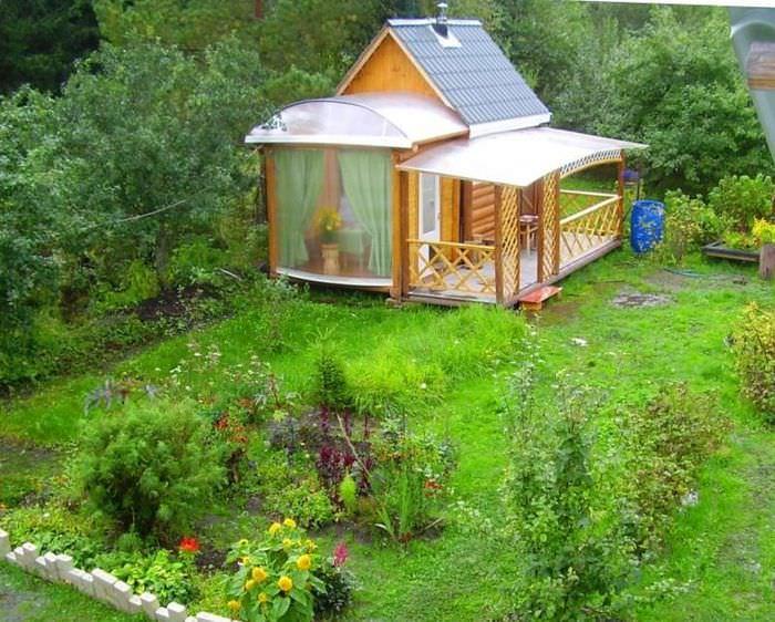 Небольшая баня в верандой в углу садового участка