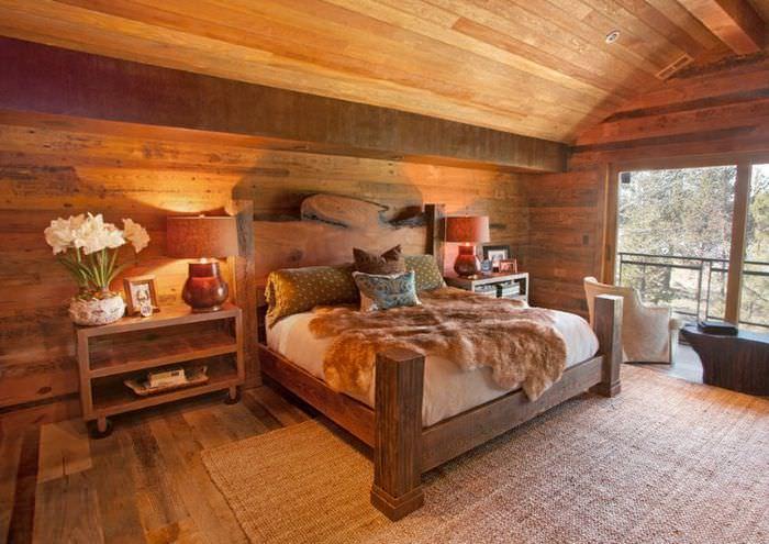 Интерьер спальни в загородном доме с отделкой натуральной древесиной