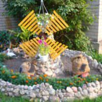 Сказочная мельница на клумбе с цветами