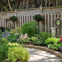 Клумба с теневыносливыми цветами перед деревянным забором