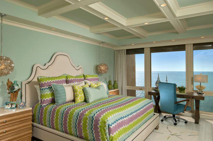Уютный дизайн спальни в мятных тонах с белыми балками на потолке