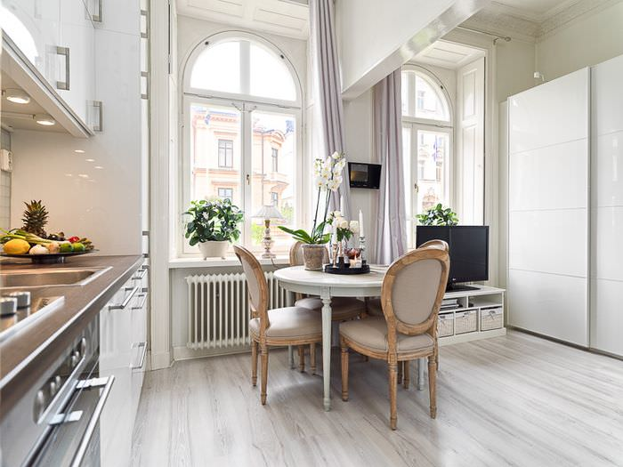 Круглый обеденный столик в совмещенной кухне-гостиной
