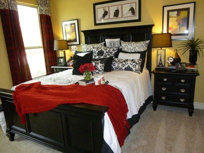 Темно-коричневая кровать в спальне с желтыми стенами