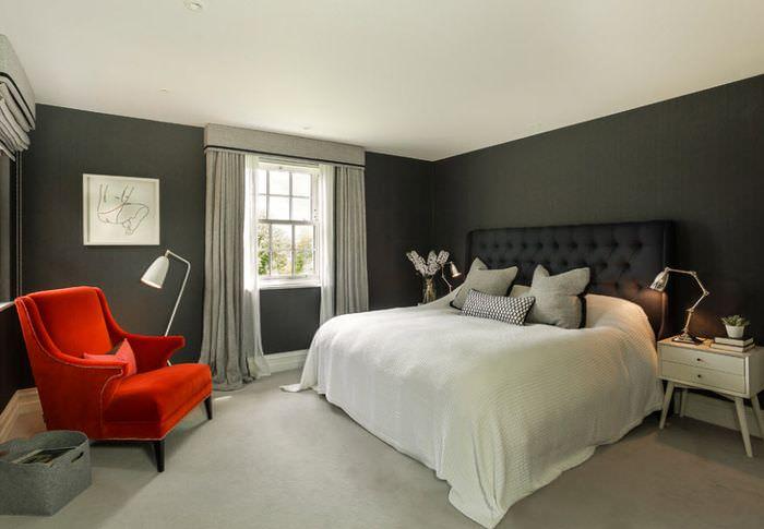 Белый балахон на черной кровати в спальне с серыми стенами
