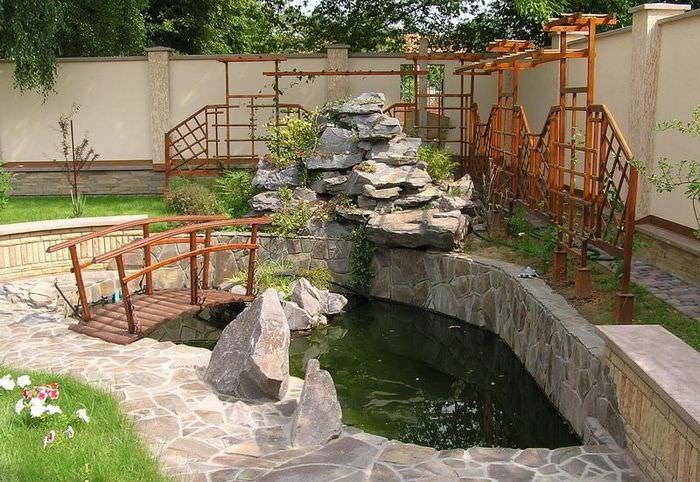 Водопад из камней перед искусственным водоемом