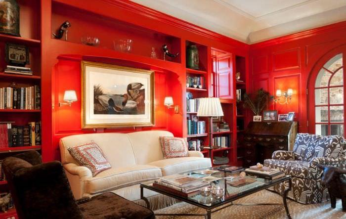 Белый диван на фоне красных стен в гостиной комнате