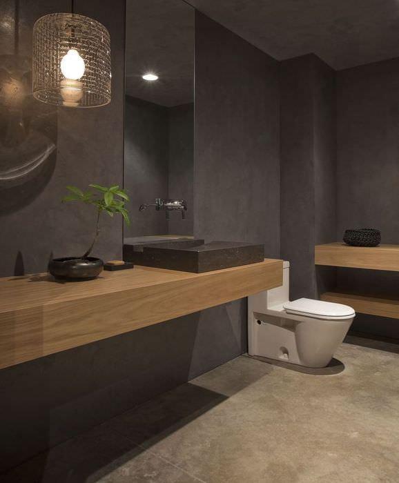 Белый унитаз в ванной комнате с коричневым интерьером