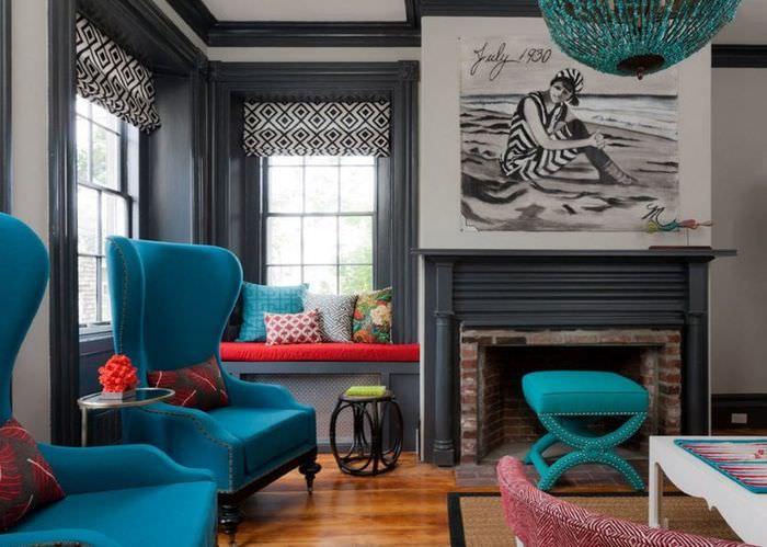 Кресла с бирюзовой обивкой и узкая полоска красной подушки на диванчике