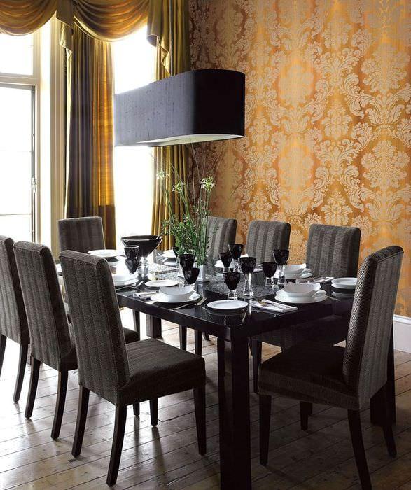 Черные стулья за обеденным столом в комнате с темно-золотыми обоями