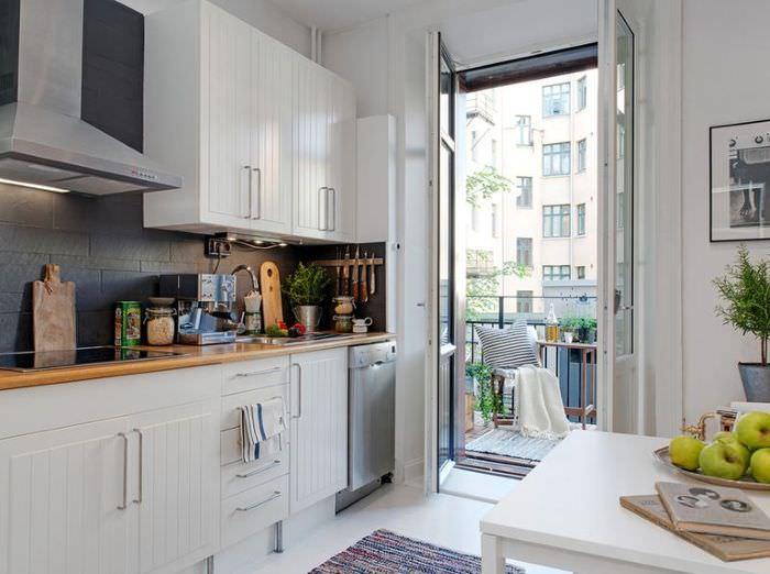Дизайн кухни с белым гарнитуром и дверью на балкон