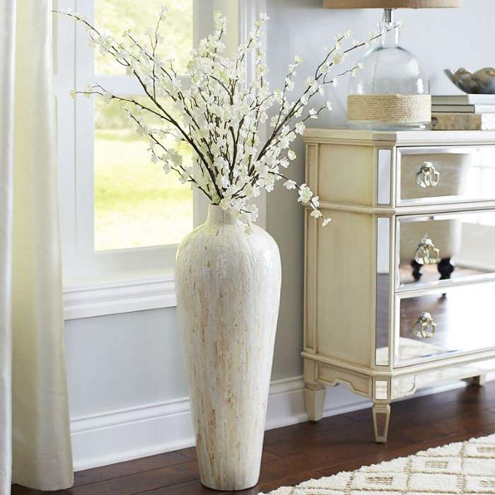 Светлая ваза с цветущими ветками рядом с винтажным комодом
