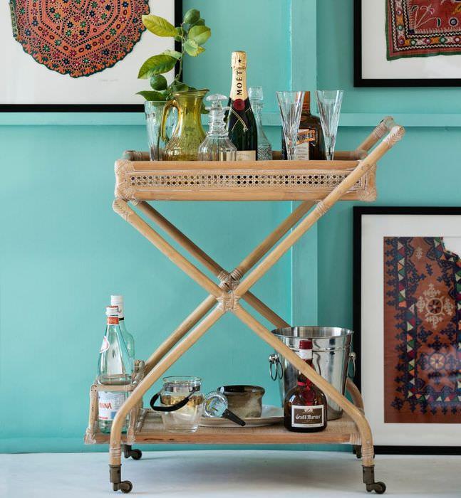 Сервировочный деревянный столик на фоне стены мятного цвета