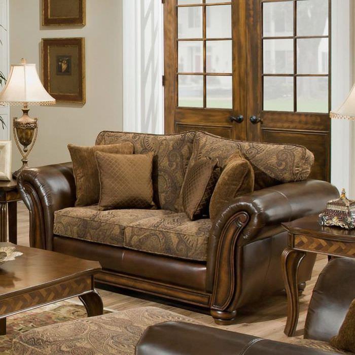 Кожаный коричневый диван на фоне деревянной двери