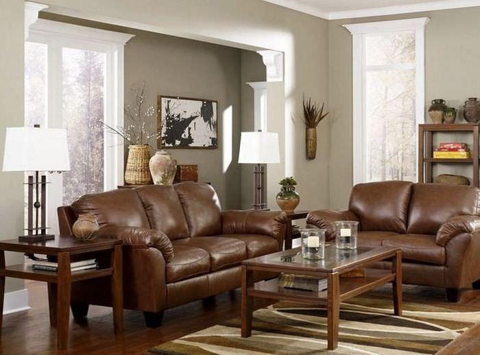 Коричневый диван из искусственной кожи на фоне светло-серых стен гостиной