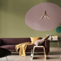 Оливковая стена за коричневым диваном