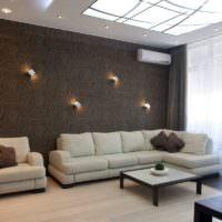 Серый диван на фоне темно-коричневой стены