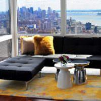 Черный диван перед панорамным окном