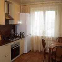 Белый двухкамерный холодильник у окна кухни