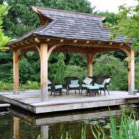 Беседка в восточном стиле на берегу садового пруда