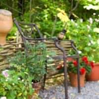 Кованный стульчик под старину в ландшафте садового участка