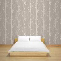 Деревянная кровать на фоне обоев с растительным принтом