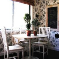 Белый обеденный столик с живыми растениями на кухне городской квартиры