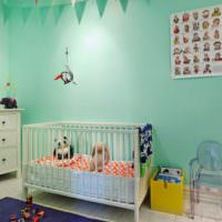 Кроватка для новорожденного перед стеной мятного цвета