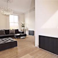 Черный радиатор отопления на белой стене
