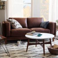 Круглый столик перед коричневым диваном