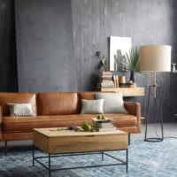 Коричневый диван в интерьере комнаты с серыми стенами