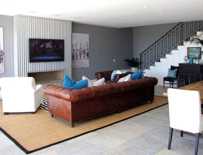 Коричневый диван с кожаной обивкой на ковре в гостиной комнате