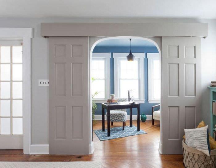 Раздвижные дверные полотна в дизайне гостиной загородного дома