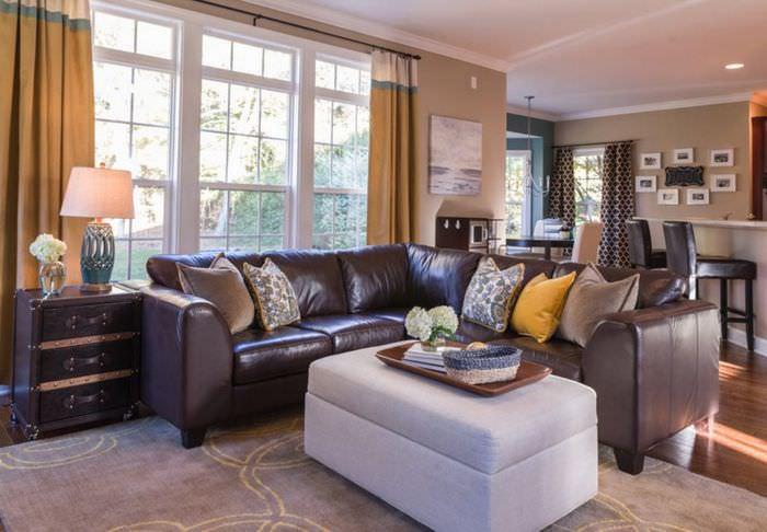 Интерьер гостиной загородного дома с коричневым диваном
