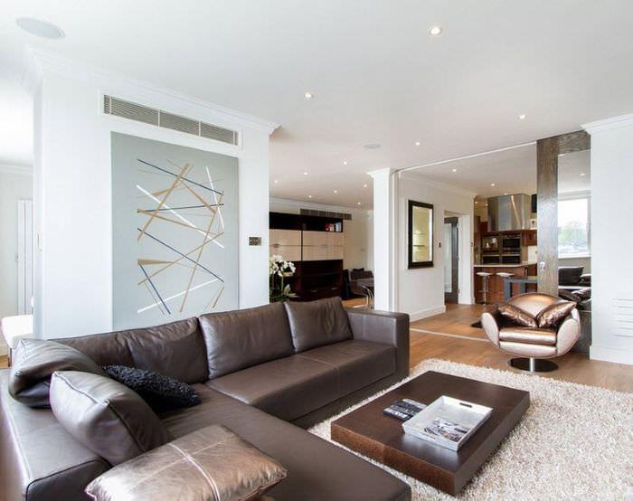 Интерьер светлой гостиной в стиле минимализма с коричневым диваном