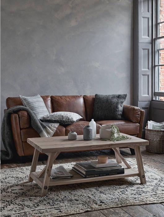 Деревянный столик перед коричневым диваном