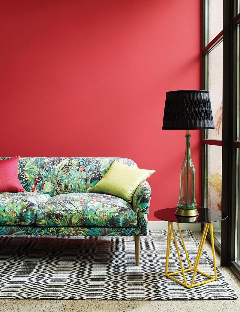 Пестрый диван на фоне красной стены