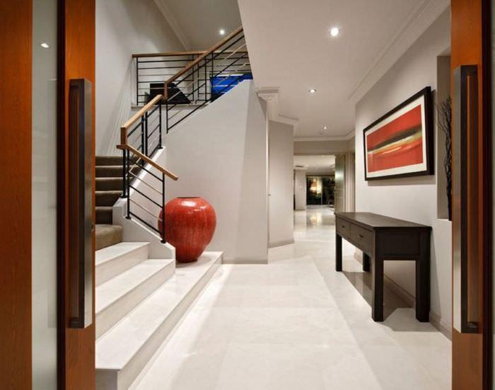 Холл частного дома с напольной вазой красного цвета