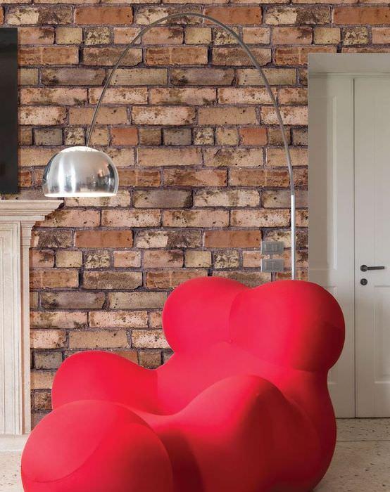 Причудливое кресло красного цвета на фоне кирпичной стены
