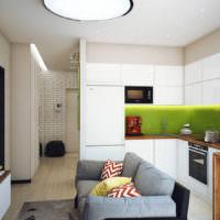 Интерьер небольшой кухни-гостиной с серым диваном
