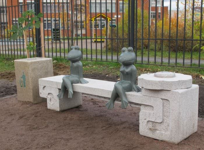 Фигурки лягушек, сидящих на декоративной скамейке