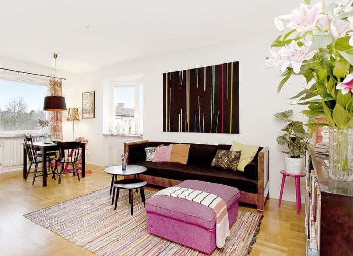 Интерьер гостиной в белом цвете с малиновым пуфом