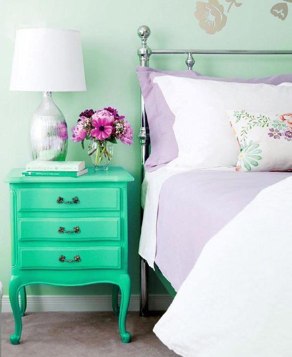 Сиреневый текстиль и прикроватная тумбочка мятного окраса в спальне частного дома