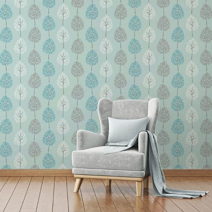 Мягкое винтажное кресло на фоне стены, отделанной обоями с природными орнаментами