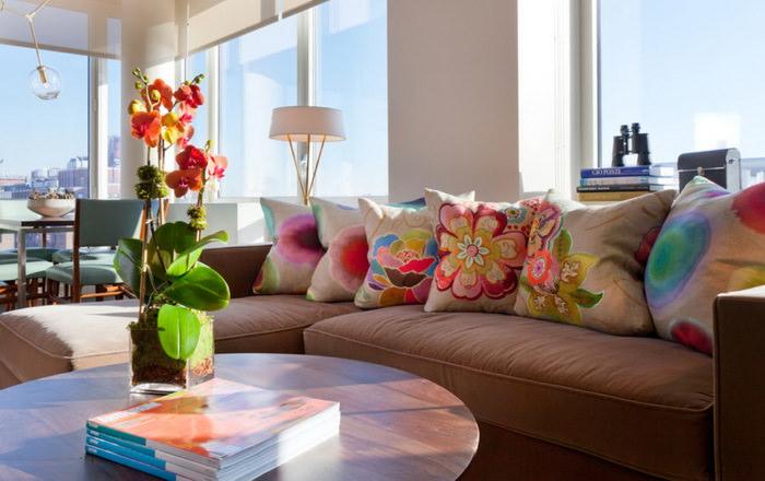 Подушки с цветами на диване коричневого окраса