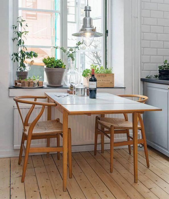 Кухонный столик с откидной поверхностью перед окном кухни частного дома