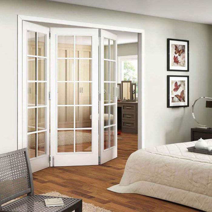 Светлые двери складной конструкции в интерьере спального помещения